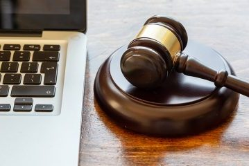 judge-gavel-and-a-laptop-wooden-background-online